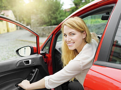 Smiling woman about to close the door and drive away in her insured car