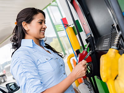 Young woman at a gas station pump