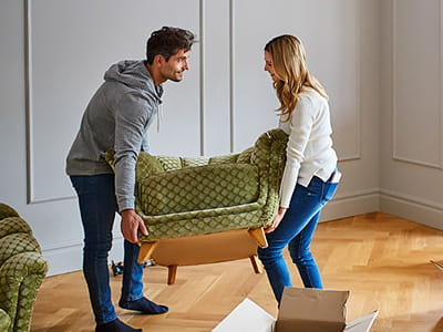Couple moving a chair and boxes