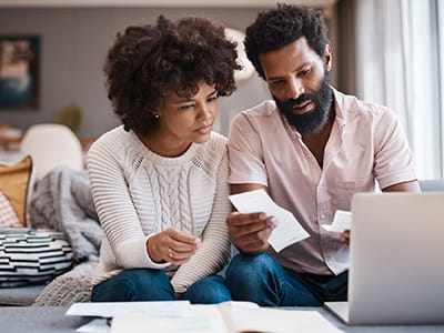 NEA Personal Loan - Couple reviewing receipts and finances together