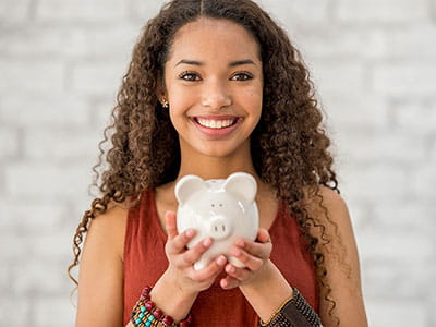 NEA Discount Marketplace - Happy young woman holding a piggy bank full of savings