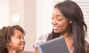 Young Woman Sharing Tablet with Child