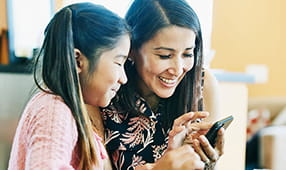 Mother and daughter taking the life insurance quiz on a mobile phone