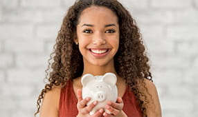 Happy young woman holding a piggy bank full of savings