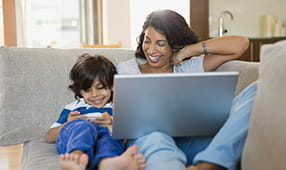 Mother and Son Playing on Personal Devices on Sofa