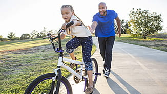 NEA Group Term Life Insurance - Father Teaching His Daughter to Ride a Bike