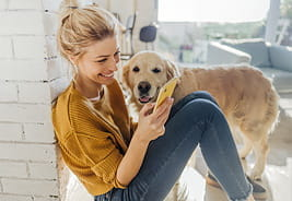 AT&T - Woman Sitting Next to Her Dog and Using Her Smartphone
