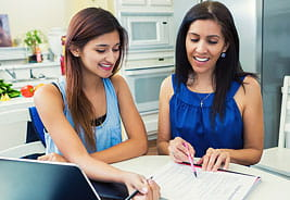 Paying for College - Mother and Teen Daughter Looking at Paperwork