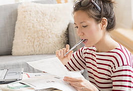 NEA Student Loan Refinance Program - Young Woman Looking at Paperwork