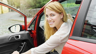NEA Auto & Home Program - Smiling Young Woman Leaning Out of the Driver's Side of Her Car