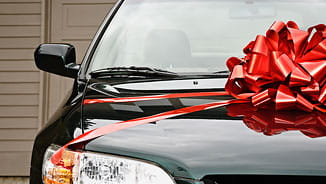 NEA Auto Buying Program - Close-Up of a Black Car with a Big Red Bow
