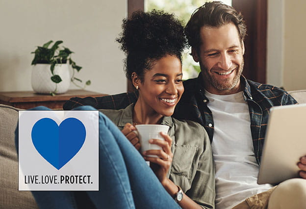 Live. Love. Protect. - image of happy couple at home reviewing information online