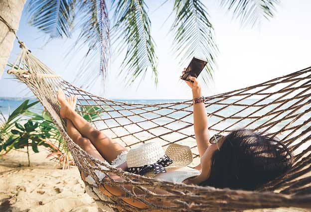 Sign Up for the NEA Travel Newsletter - Woman with Mobile Phone Relaxing in a Hammock