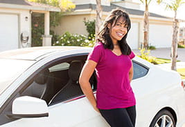 Woman smiling while she leans against her car in front of her home