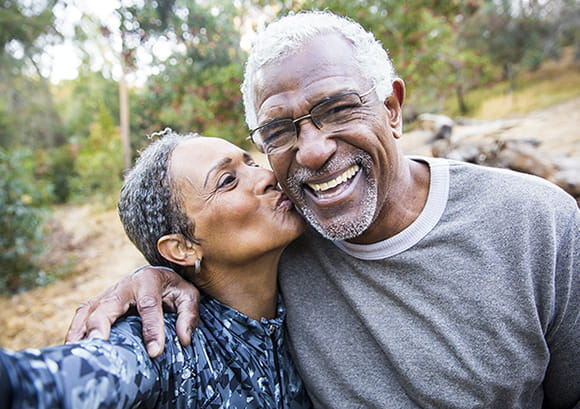 Older couple - Husband smiling when wife gives him a kiss on the cheek