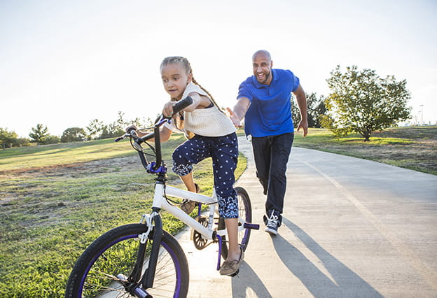 Father teaching daughter to ride her bike