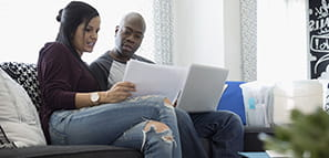 Couple Using a Laptop and Reviewing Financial Statements.