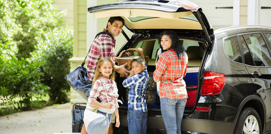 Family packing car to go on vacation. Parents, children.