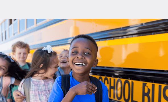 Elementary school children wait in line by the school bus